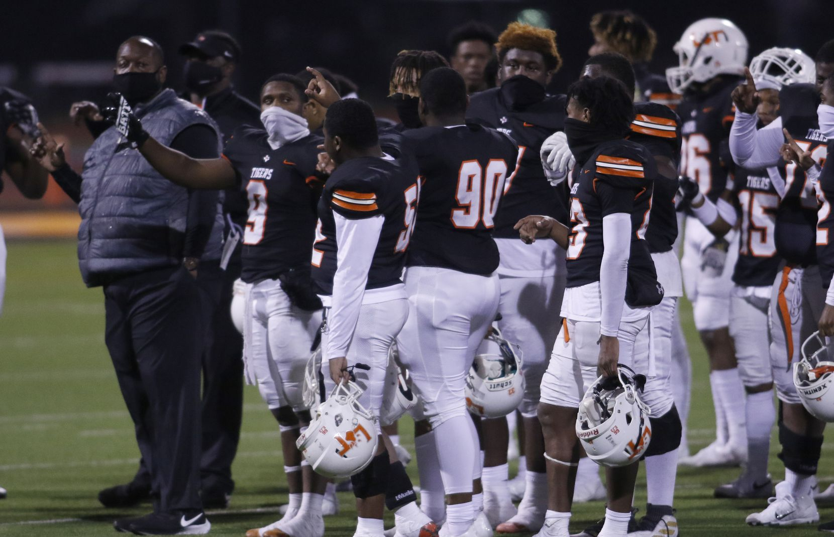 Lancaster head coach Chris Gilbert pauses with his Tigers players for the playing of their school song after their victory over Dallas Woodrow Wilson. The two teams played their District 6-5A Division 1 football game at Beverly D. Humphrey Tiger Stadium in Lancaster on November 20, 2020. (Steve Hamm/ Special Contributor)