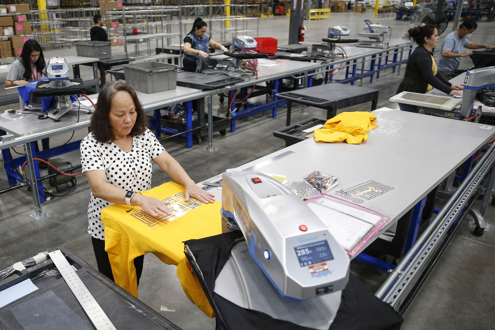 Workers fulfill custom design apparel orders at BSN Sports on May 7 in Grand Prairie.