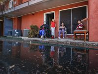 (L to R) Modesta Gonzalez, 60, Deveany Mendoza, 10, Alina Mendoza, 6, and Guadelupe Mendoza, 4, are reflected in water that flooded their their apartment from frozen pipes during last weeks severe cold, at the Villas de Solamar apartments in Dallas, Wednesday, February 24, 2021.