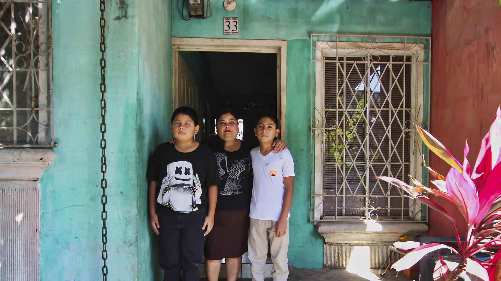 Flor Tovar y sus hijos Christian (derecha) y Oma Elias posan afuera de su casa en Ciudad Real, El Salvador. AP.