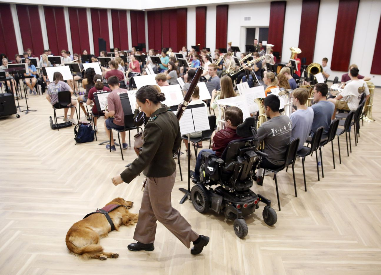 Texas A&M graduate student Kyle Cox (right in wheelchair), who has Duchenne Muscular Dystrophy, warms up his baritone before symphonic band rehearsal at the new Music Activities Center on the Texas A&M campus in College Station, Texas, Wednesday, September 11, 2019. He was joined by his golden retriever service dog, Amber.