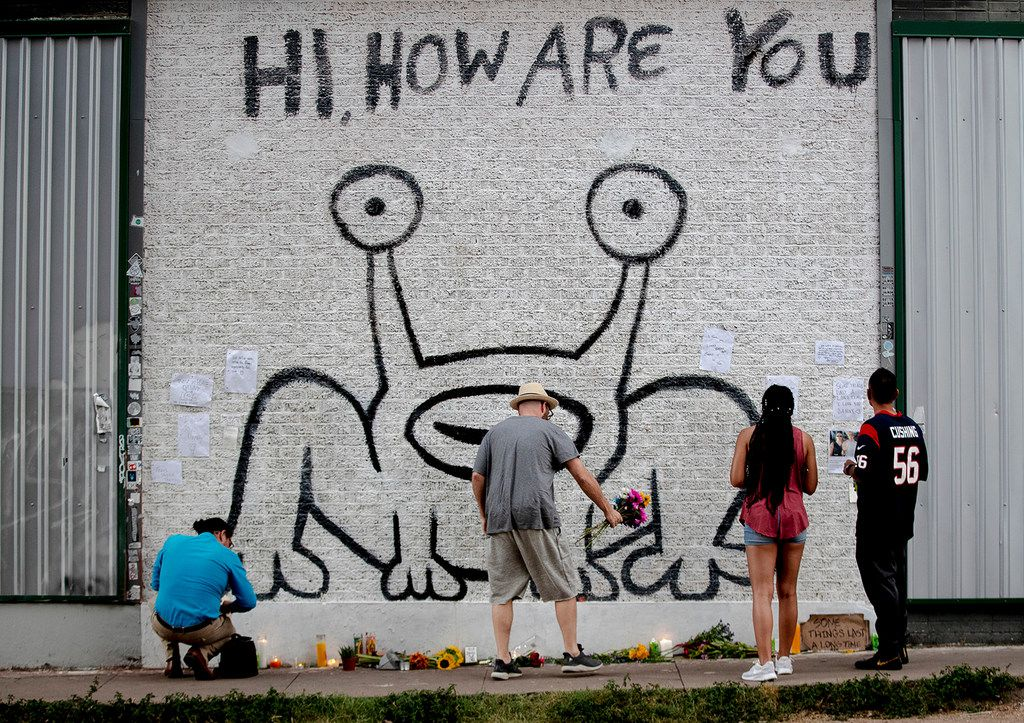 """A man places flowers beneath the """"Hi, How Are You"""" mural created by artist Daniel Johnston on Wednesday, Sept. 11, 2019, in Austin, Texas. Johnston, a quirky folk singer-songwriter and visual artist whose offbeat career and struggles with mental illness brought him a cult following and inspired a documentary film, has died Wednesday at age 58."""