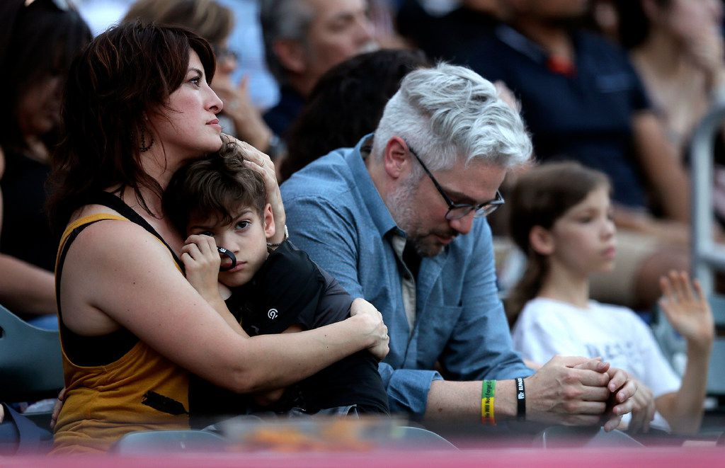 Valerie Bowers along with her son Jude Bowers and Husband Eric Bowers react as they watch a slideshow of the victims of the Aug. 3 mass shooting at a community memorial service, Wednesday, Aug. 14, 2019, at Southwest University Park, in El Paso, Texas.