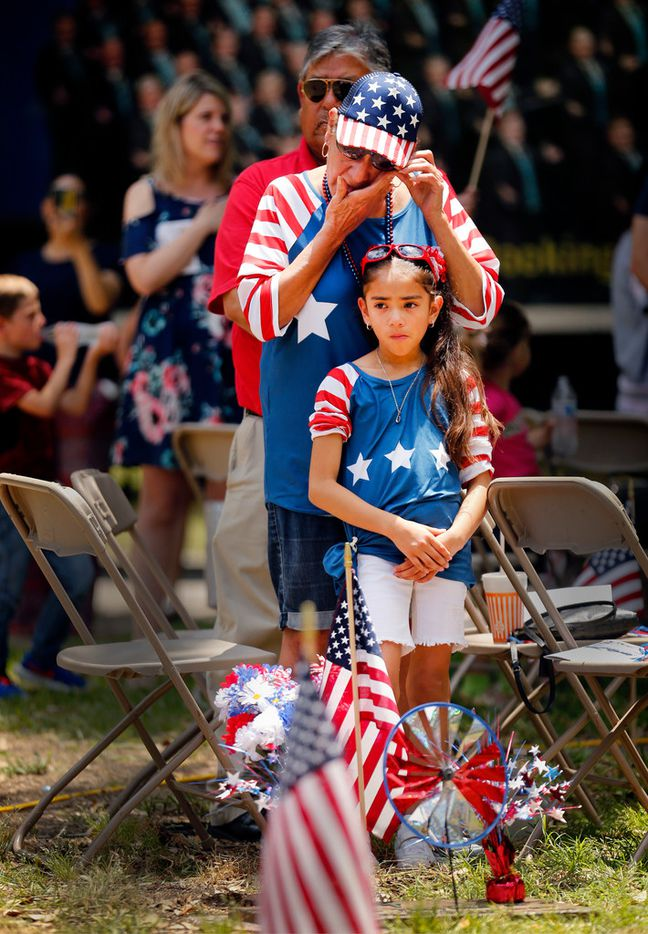 At the foot of her husband's grave, Erlinda Trevino of Mesquite wiped away tears as Taps was played during Monday's Memorial Day ceremony at Restland Memorial Park in Dallas. With her was niece Secilia Guzman. Trevino's husband, Savas E. Trevino, Sr., a Marine Corps private first class, was killed in the Vietnam war in 1969.
