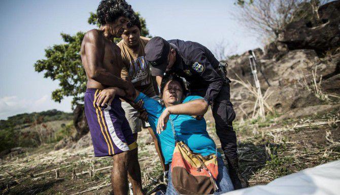 Una mujer se desmaya luego de identificar el cadá ver de su hermano asesinado, en Caserío el Chumpe, El Salvador. El hombre fue secuestrado y asesinado por pandilleros. (AP/MANU BRABO)