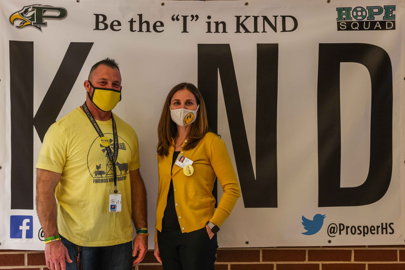 Coach Tony Cooper and Alexis Webb, the PISD point person for Hope Squad, stand with a Hope Squad banner in the Prosper High School lobby.
