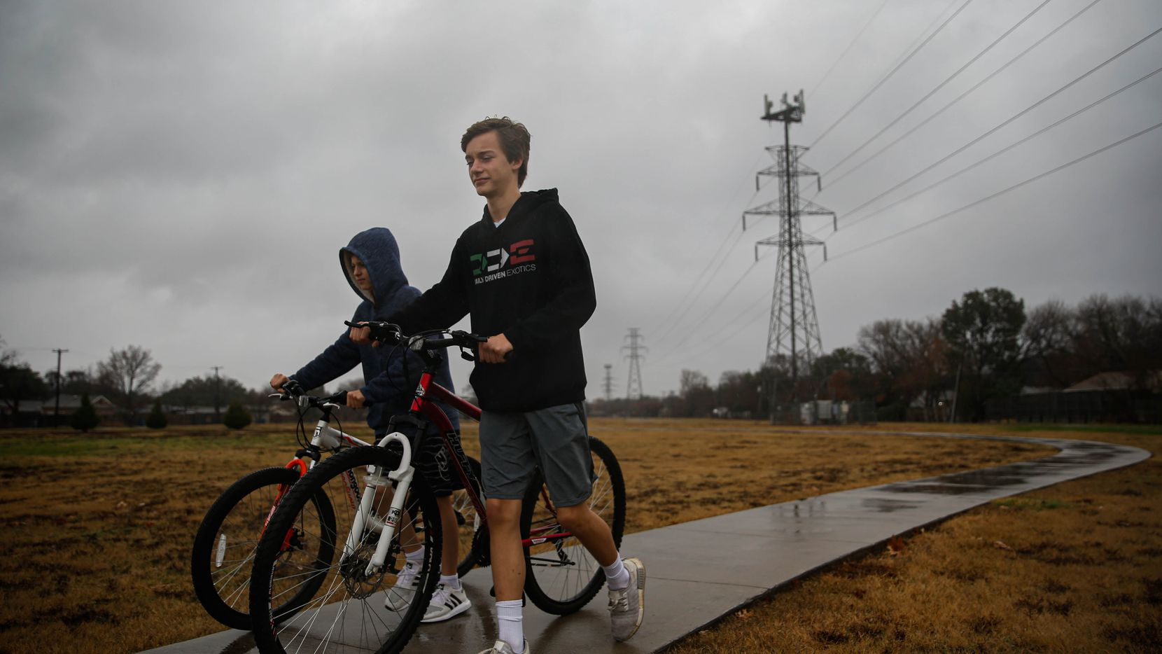 (From left) Henry Webb, 11, and his brother Jack, 14, walk to their mother's SUV after getting stuck in the rain at Royal Park on Dec. 28, 2019 in Dallas.
