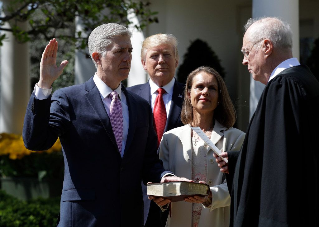 President Donald Trump watches as Supreme Court Justice Anthony Kennedy administers the judicial oath to Judge Neil Gorsuch in the Rose Garden on April 10, 2017. Holding the bible is Gorsuch's wife Marie Louise Gorsuch.