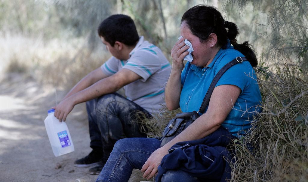 In this Aug. 11, 2017, photo, immigrants suspected of crossing into the United States illegally along the Rio Grande near Granjeno, Texas, are held by U.S. Customs and Border Patrol agents. The election of President Donald Trump contributed to a dramatic downturn in migration, causing the number of arrests at the border to hit an all-time low in April. But since bottoming out last spring, the number of immigrants caught at the southern border has been increasing monthly.
