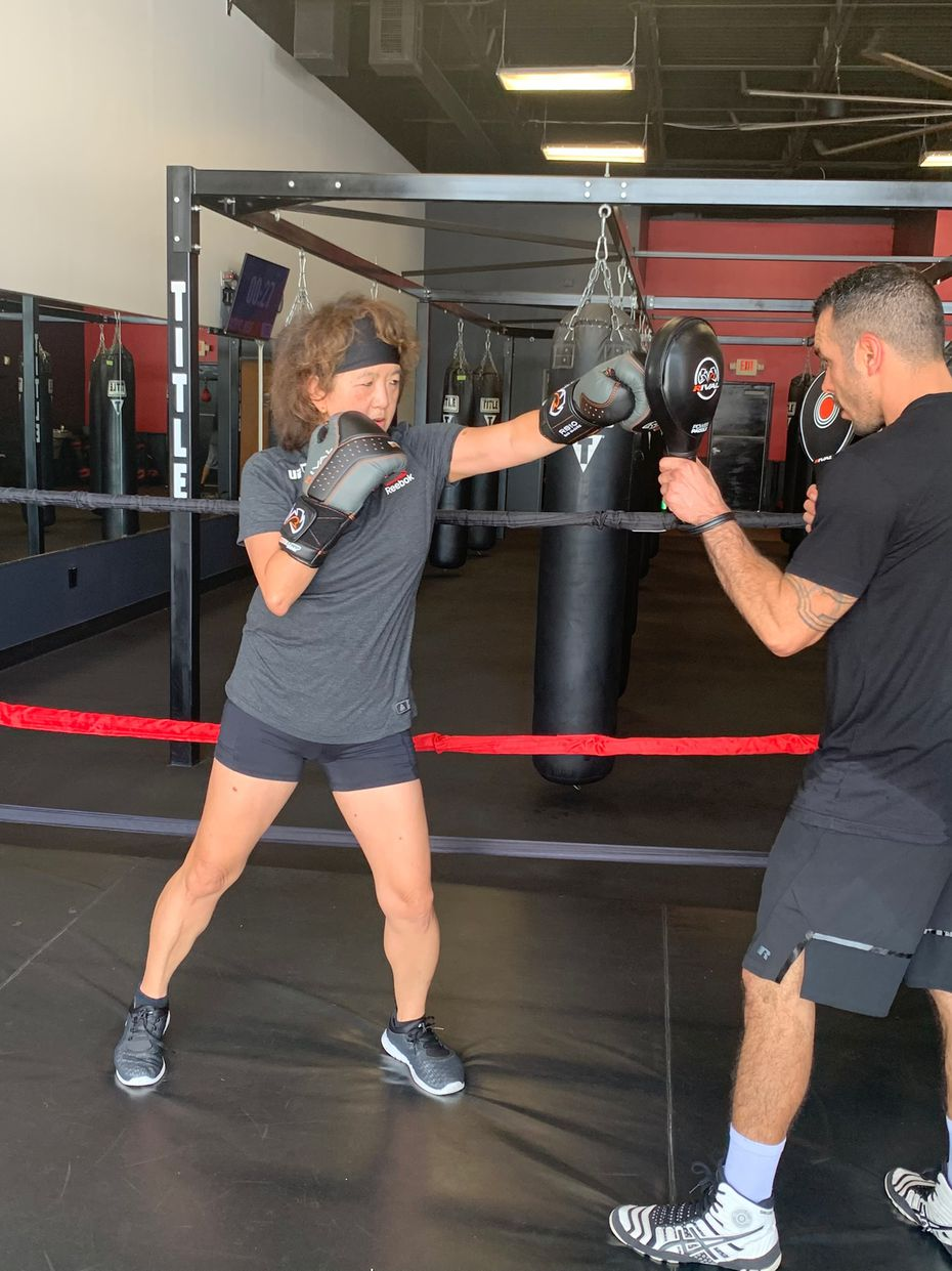 Anne Chow, CEO of AT&T Business, works out with trainer Christafer Duran at Title Boxing Club Plano.