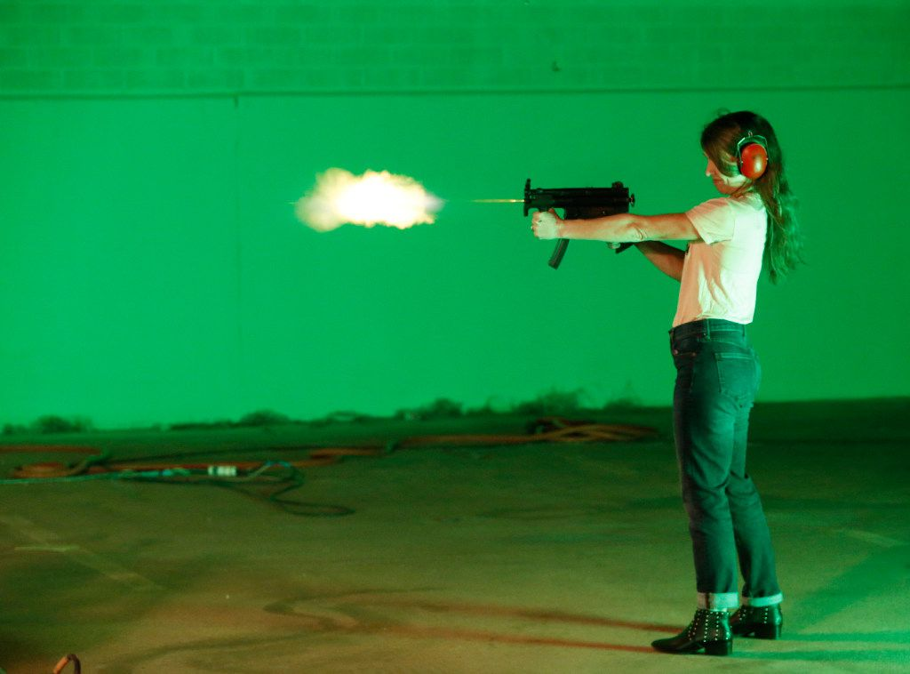 "Natalie Chaidez, a ""Queen of the South"" show runner, tries out a machine gun during filming at South Side Studios in Dallas on May 25."