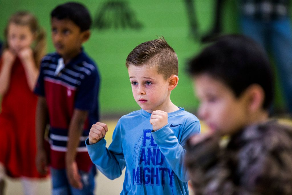 Jett Foster and other kindergarten students participate in a martial arts class.