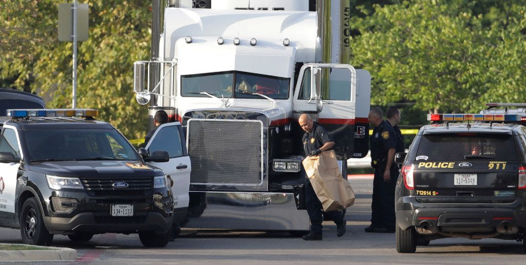 San Antonio police officers investigate the scene where eight people were found dead in a tractor-trailer loaded with at least 30 others outside a Wal-Mart store in what police are calling a horrific human smuggling case.