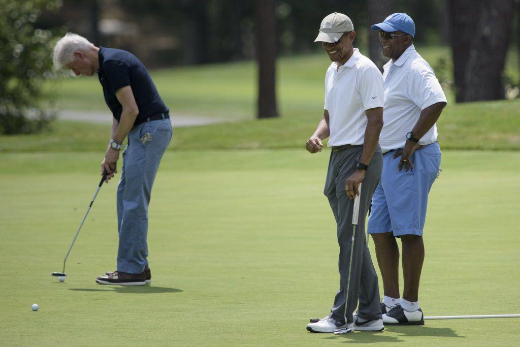 President Barack Obama and Ron Kirk talk as former President Bill Clinton putts at Farm Neck Golf Club on Saturday in Oak Bluffs, Mass., on Martha's Vineyard. (AFP photo/Brendan Smialowski)