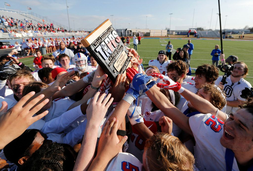 Parish Episcopal's football team hoists the trophy after receiving it during the awards presentation after defeating Plano John Paul II 42-14 in the TAPPS Division I State Championship game at Waco Midway's Panther Stadium in Hewitt, Texas on Friday, December 6, 2019. (Vernon Bryant/The Dallas Morning News)