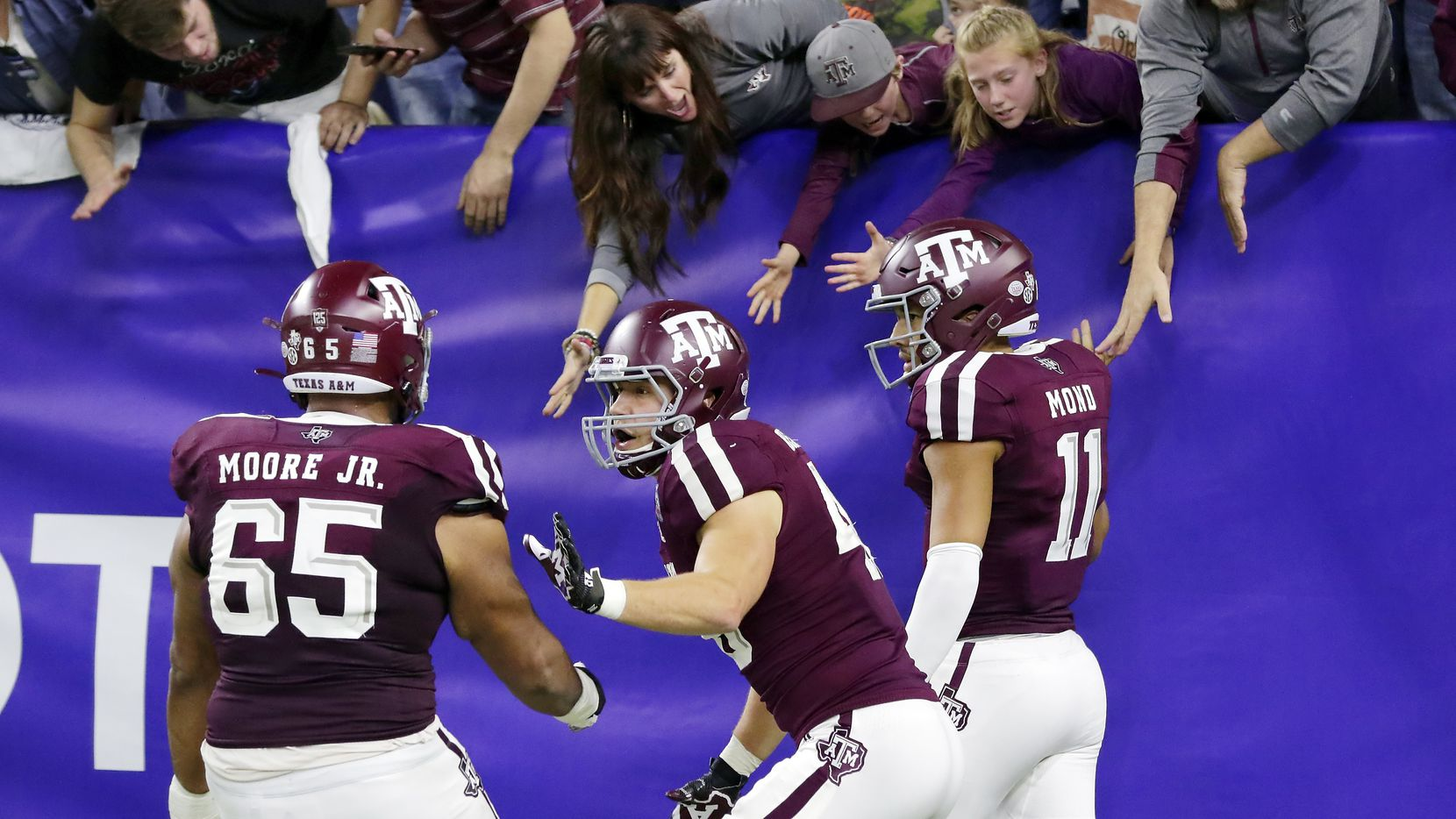 Texas A&M offensive lineman Dan Moore Jr. (65) and tight end Ryan Renick, middle, celebrate as quarterback Kellen Mond (11) high-five fans in the stands after Mond's touchdown during the second half of the Texas Bowl NCAA college football game against Oklahoma State on Friday, Dec. 27, 2019, in Houston.