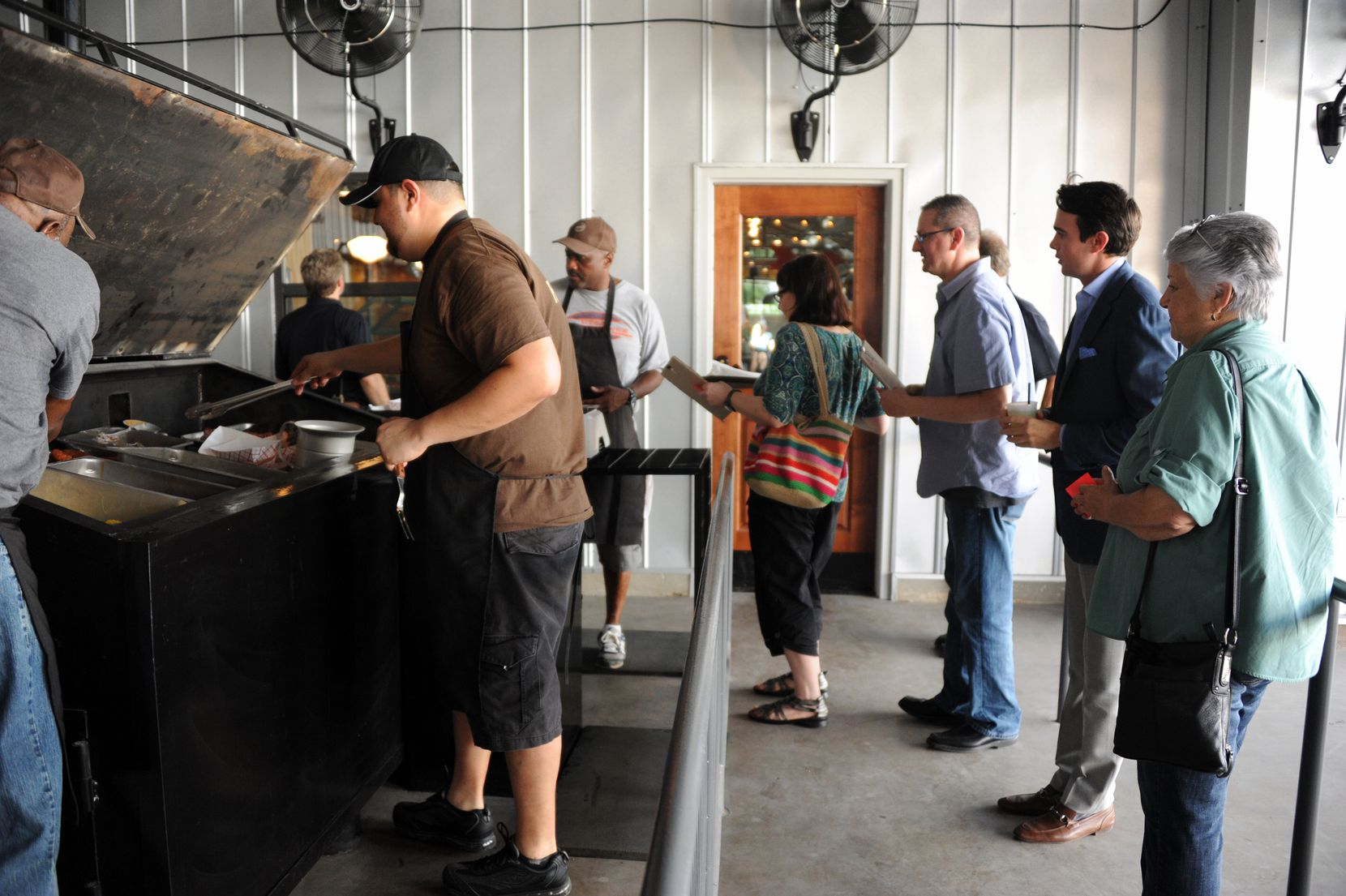 Guests form a line to order meats from the smoker at Ten 50 BBQ in Richardson.