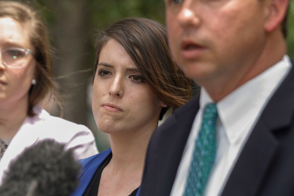 Julie Vazquez, left, wife of Mansfield Independent School District art teacher, Stacy Bailey, center, listen to their lawyer, Jason Smith, announce a lawsuit has been filed against the Mansfield ISD for discrimination at a press conference held at Belo Gardens in downtown Dallas, Tuesday, May 8, 2018.  Bailey was suspended with pay last September after her sexual orientation was disclosed to students at Charlotte Anderson Elementary School.