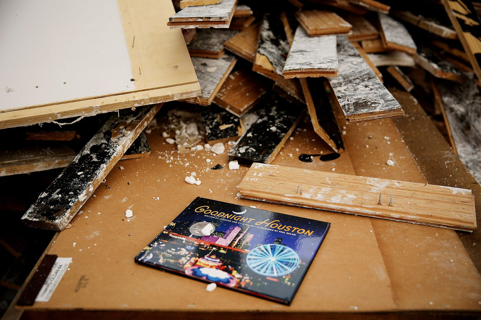 """One Meyerland area family left a book titled Goodnight Houston on a heap of damaged furniture. The family's last name and """"2017"""" were carved into the curb next to the driveway."""