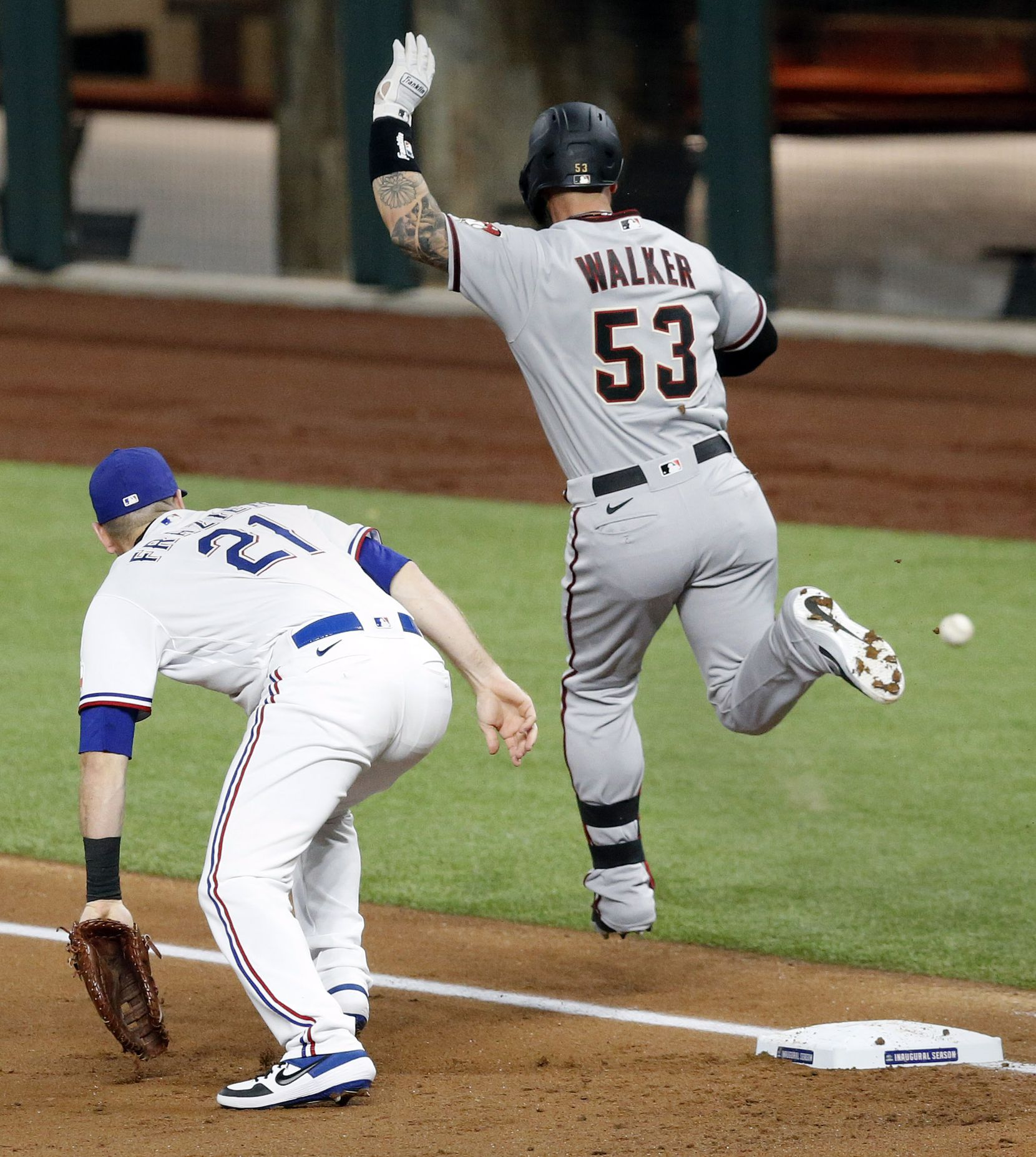 The ball gets away from Texas Rangers first baseman Todd Frazier (21) on a throw from third baseman Isiah Kiner-Falefa (9) during the first inning at Globe Life Field in Arlington, Texas, Tuesday, July 28, 2020. Walker advanced second as two runs scored. (Tom Fox/The Dallas Morning News)