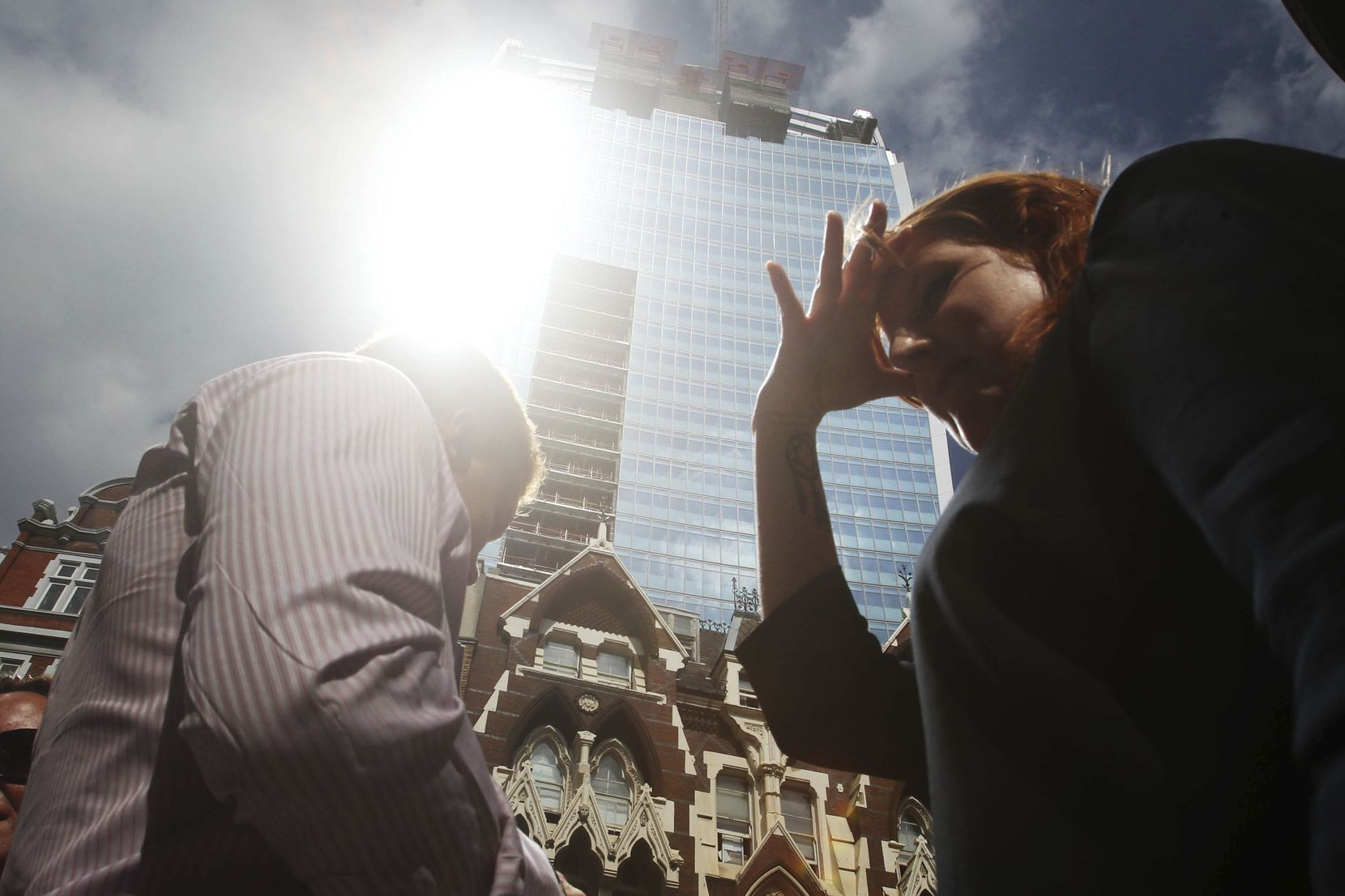 A woman shields her eyes as sunlight is reflected off the so-called Walkie Talkie building in London, in September 2013, before its glare issues were addressed.