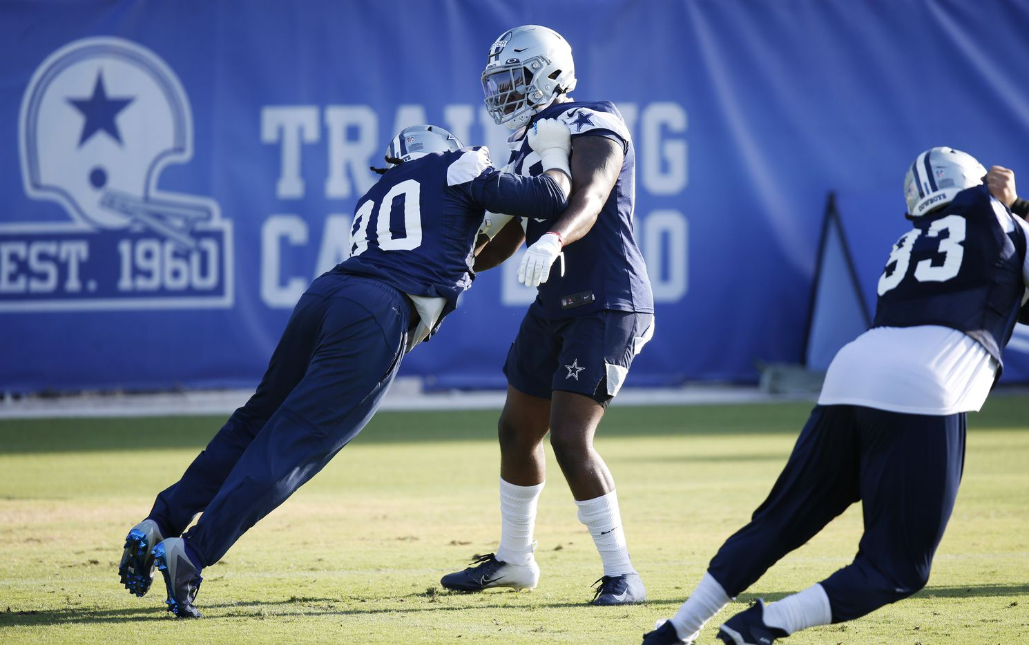 Dallas Cowboys defensive end DeMarcus Lawrence (90) and Dallas Cowboys defensive end Ron'Dell Carter (68) work through a drill during the first day of training camp at Dallas Cowboys headquarters at The Star in Frisco, Texas on Friday, August 14, 2020.