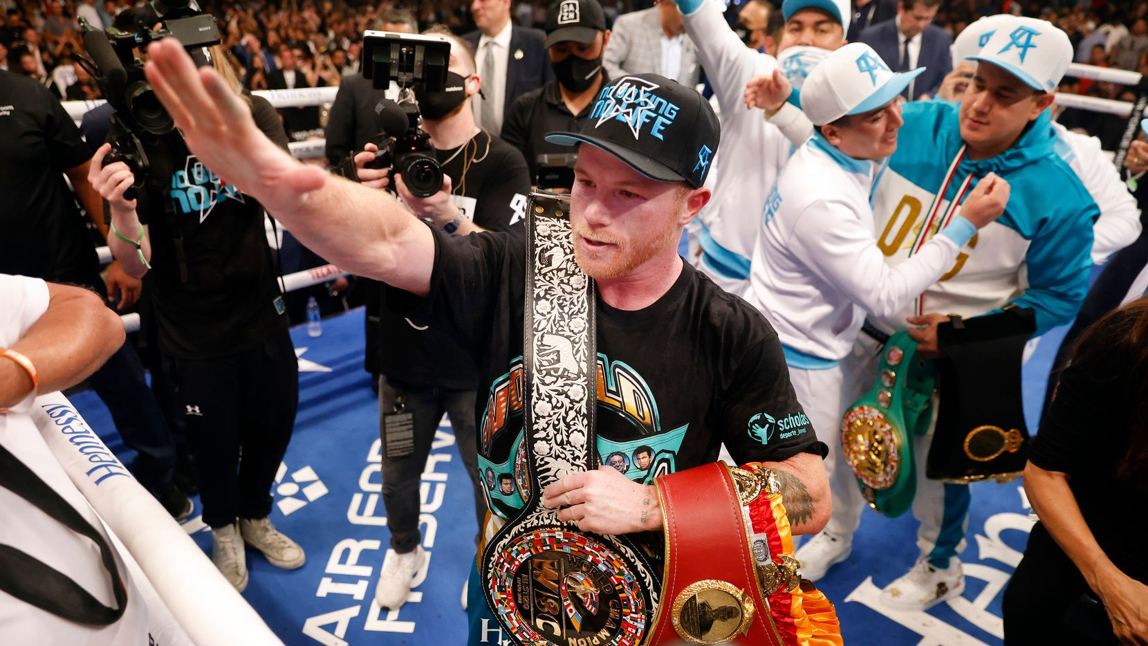 """Los boxeadores Saúl """"Canelo"""" Álvarez saludan al público mientras celebra con sus cinturones después de derrotar a Billy Joe Saunders en su pelea por el título unificado de peso súper mediano en el AT&T Stadium en Arlington, el sábado 8 de mayo de 2021."""