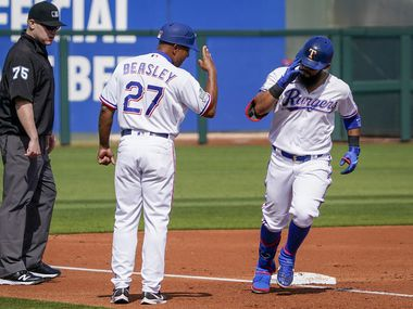 Texas Rangers third base coach Tony Beasley salutes second baseman Rougned Odor as he rounds the bases after hitting a grand slam home run during the first inning of a spring training game against the Chicago Cubs at Surprise Stadium on Thursday, Feb. 27, 2020, in Surprise, Ariz.