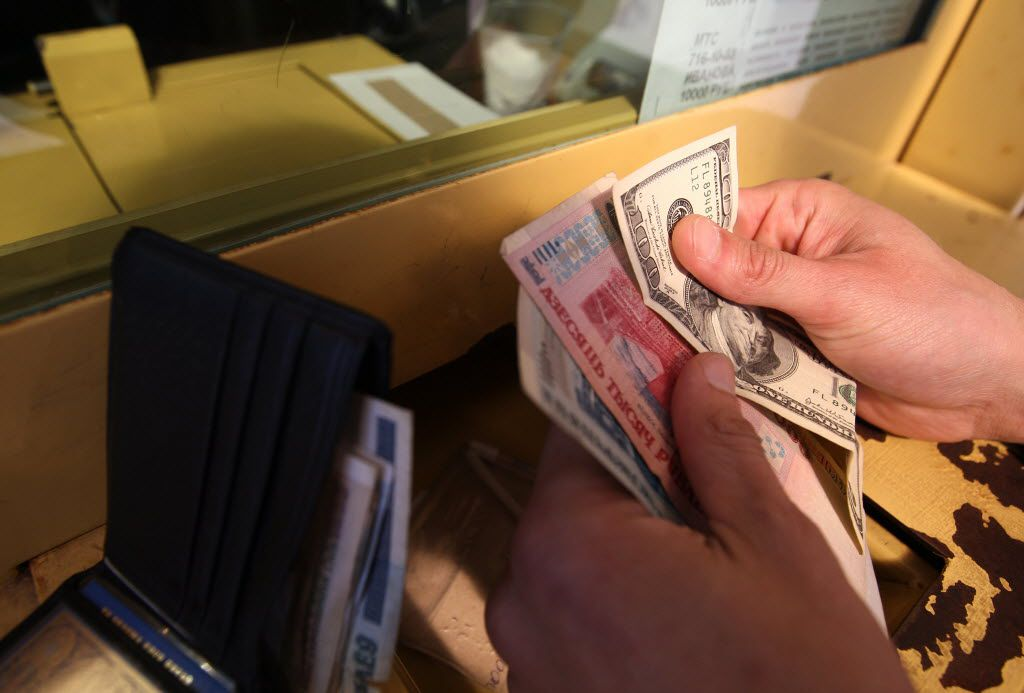 A man exchanges money at the currency exchange desk of a bank in Minsk.