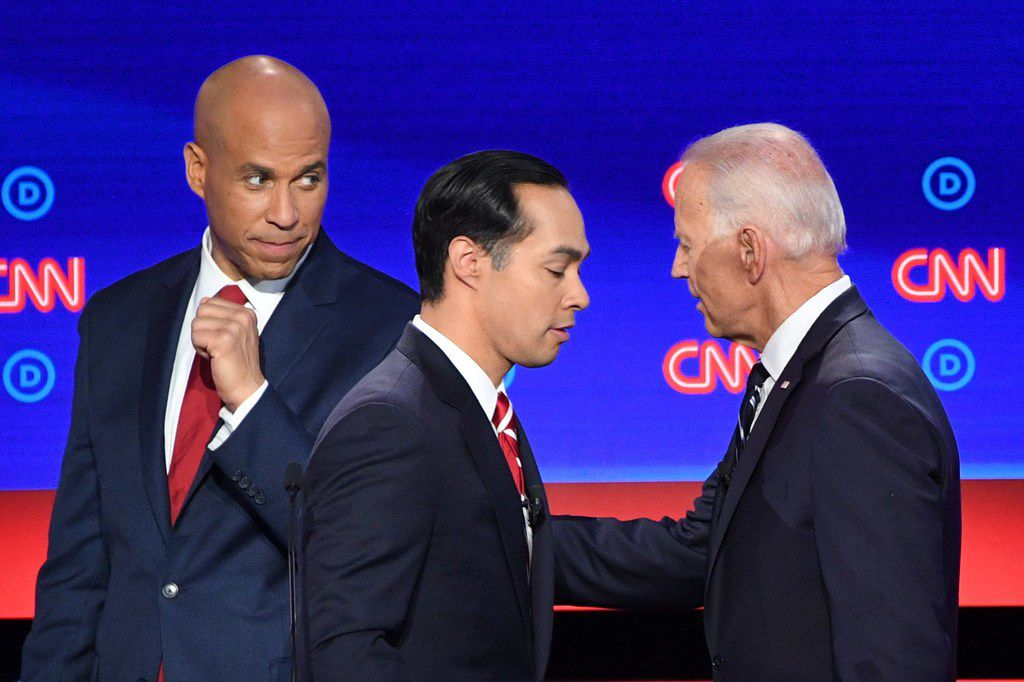 Democratic presidential hopefuls U.S. Sen from New Jersey Cory Booker (left), Former U.S. Secretary of Housing and Urban Development Julián Castro and former Vice President Joe Biden chat during a break in the second round of the second Democratic primary debate of the 2020 presidential campaign season hosted by CNN at the Fox Theatre in Detroit, Mich., on July 31, 2019.