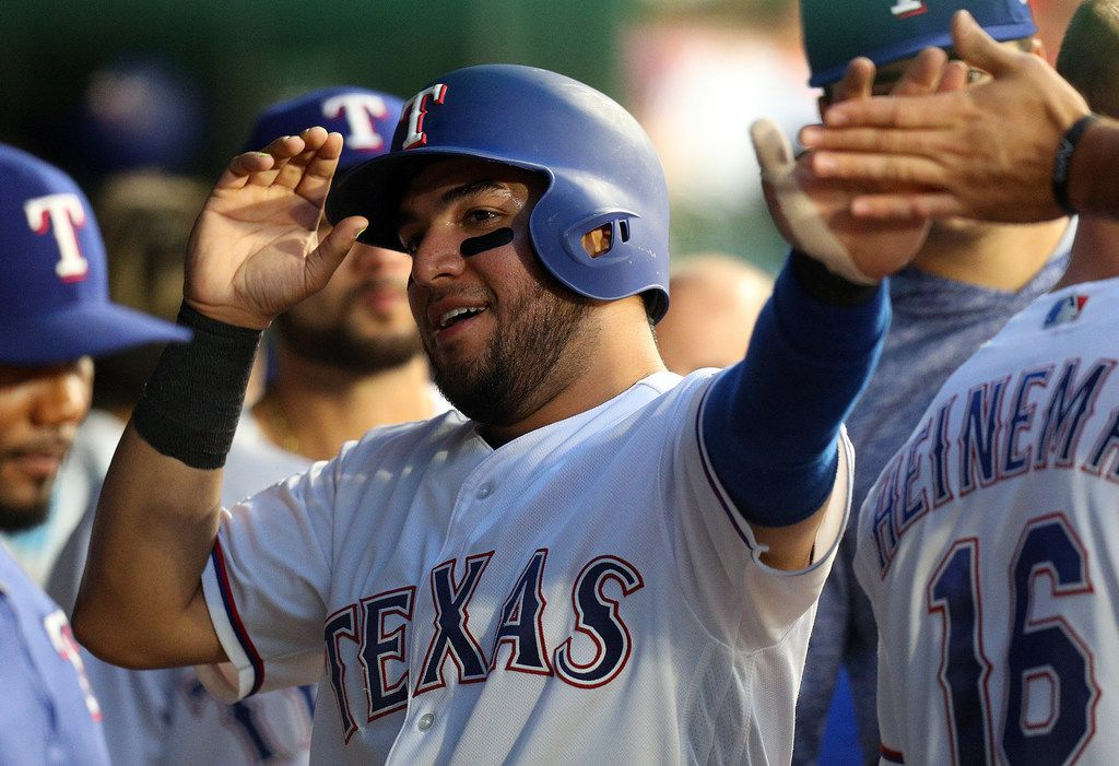 ARLINGTON, TEXAS - AUGUST 30: Jose Trevino #56 of the Texas Rangers is greeted in the dugout after scoring on a sacrifice fly by Willie Calhoun #5 in the third inning against the Seattle Mariners at Globe Life Park in Arlington on August 30, 2019 in Arlington, Texas. (Photo by Richard Rodriguez/Getty Images)