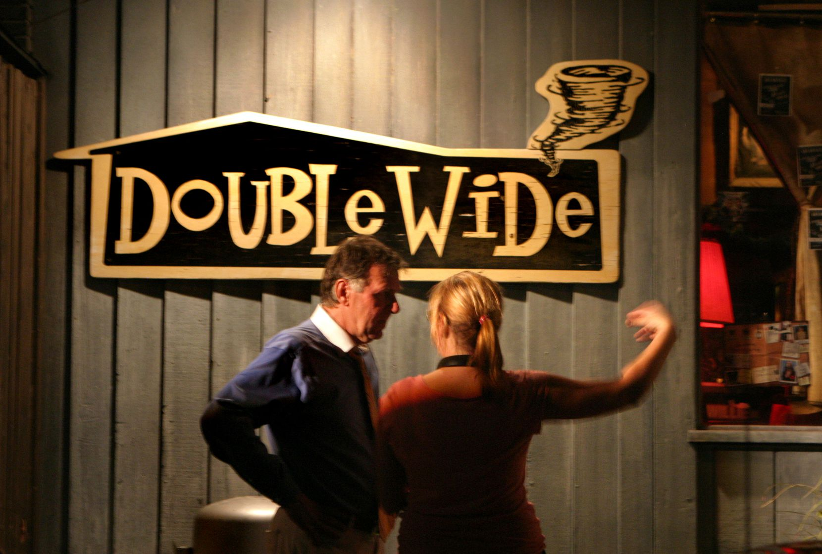"""Amy Talkington (right) gives actor Tom Wilkinson direction before a scene at the Double Wide bar in the film """"The Night of the White Pants."""""""