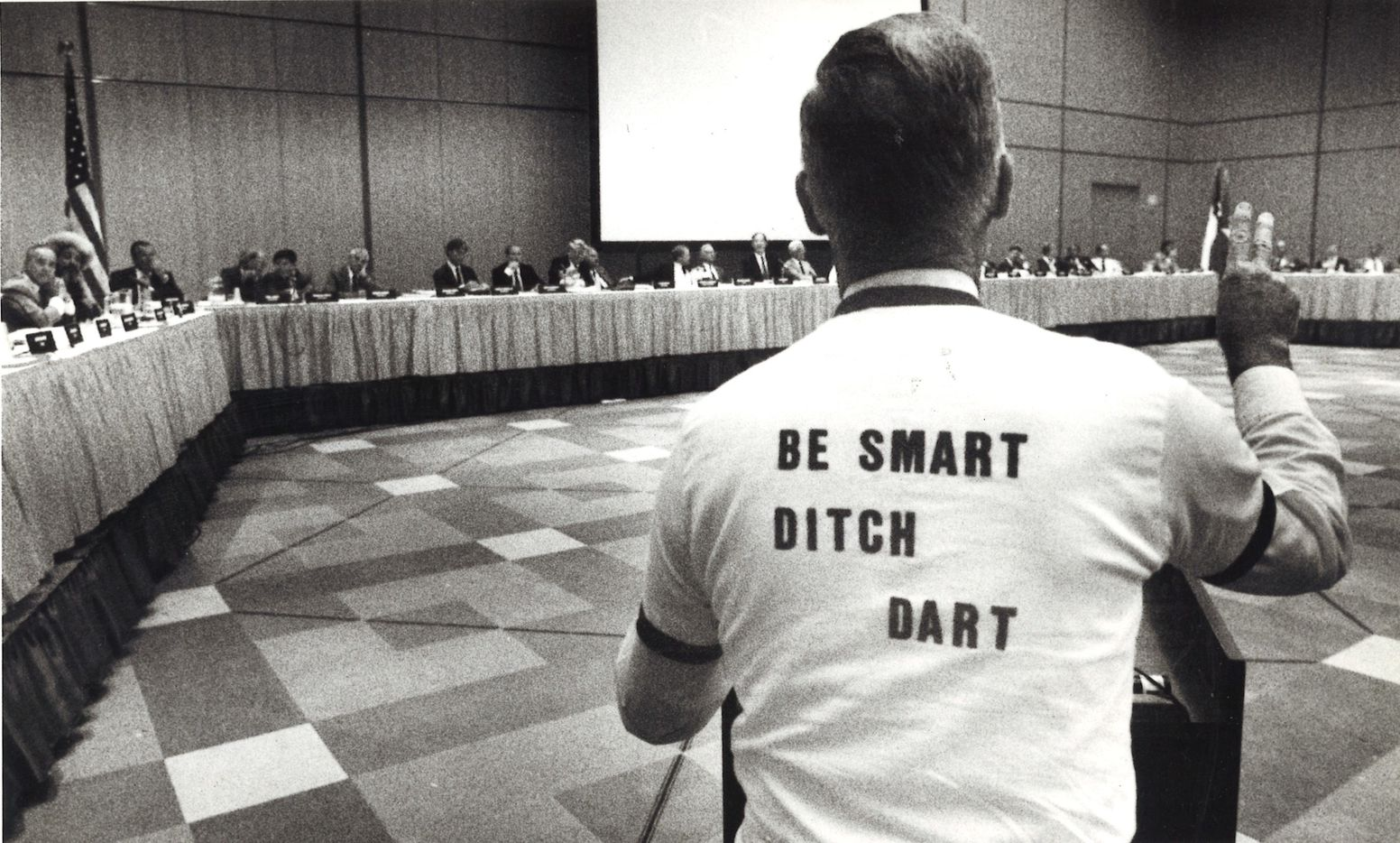 """Dewayne Dallas wears a T-shirt """"Be Smart, Ditch Dart"""" while speaking at a public hearing at the Dallas Convention Center in 1985."""