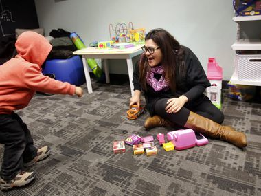 In this file photo, Laura De La Paz (right) plays with a child in the children's playroom at the Genesis Women's Shelter & Support Outreach Counseling Center. The shelter works with women and children who are fleeing domestic violence. (Tom Fox/The Dallas Morning News)