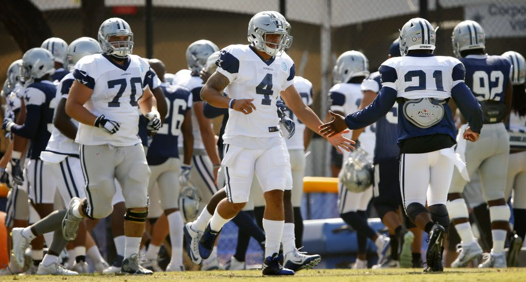 With Dallas Cowboys quarterback Tony Romo out of practice today, quarterback Dak Prescott (4) took the first team role as he slaps hands with fellow rookie Ezekiel Elliott (21) during afternoon practice at training camp in Oxnard, California, Thursday, August 4, 2016. (Tom Fox/The Dallas Morning News)