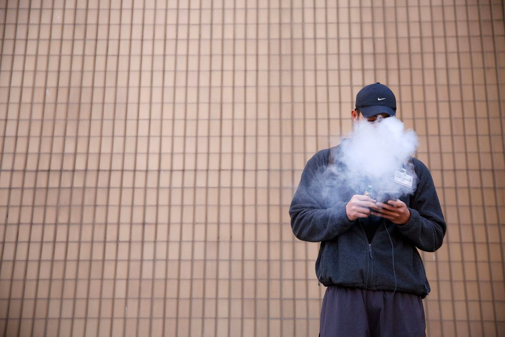 "Tommy Nguyen, 27, vapes outside El Centro College in downtown Dallas on Monday, March 18, 2019. GOP leaders of powerful committees in the Texas House and Senate are again lead authors of proposals that would raise the legal age for buying cigarettes, other tobacco products and e-cigarettes from 18 to 21. Nguyen thinks the legal age shouldn't be raised for vaping products. ""I come from a family full of smokers and now they're smoking less because of vaping,"" Nguyen said. (Rose Baca/Staff Photographer)"