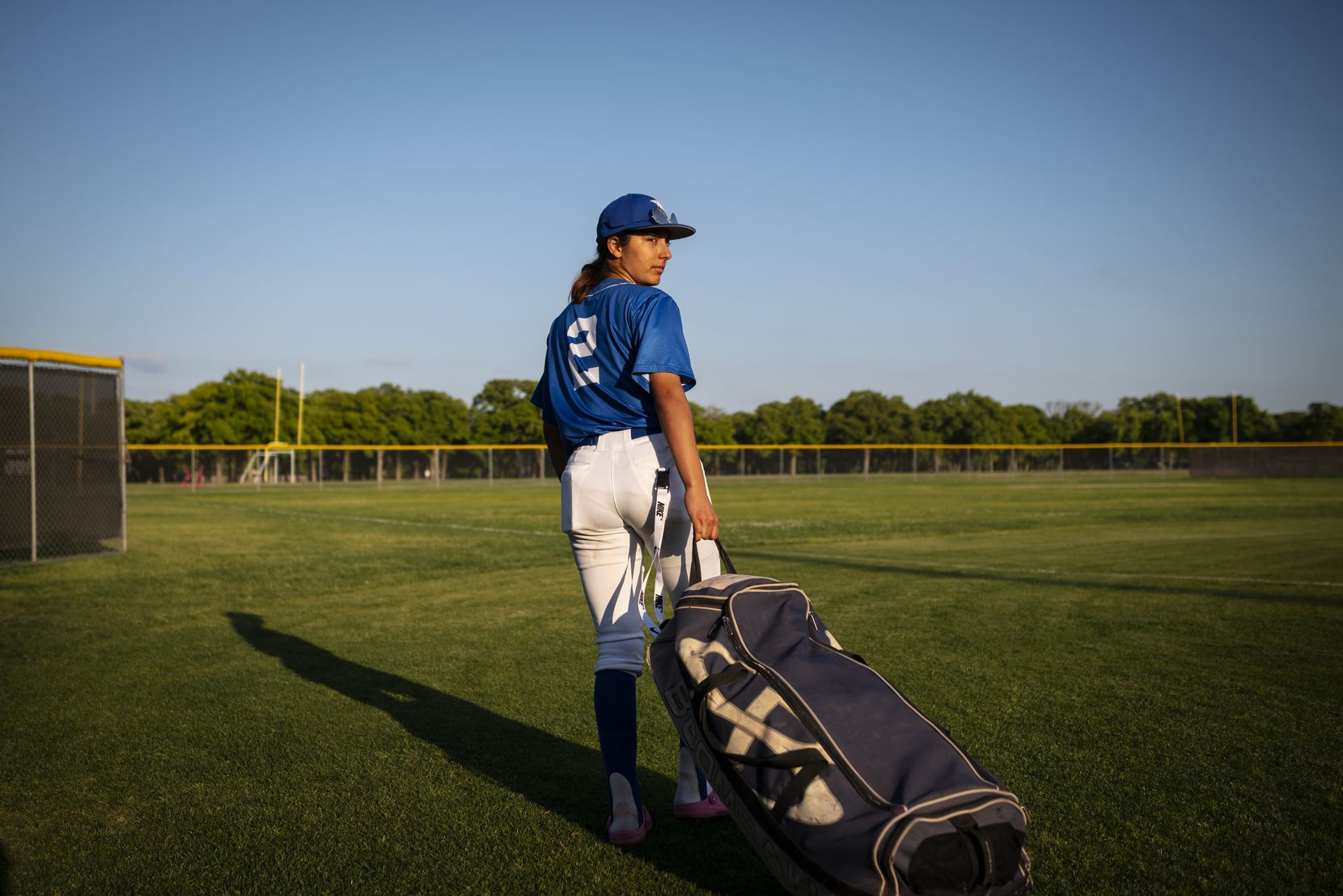 Adamson High School senior Tatyana Beltran (2), looks back as she walks off the field saying goodbye to her coach and teammates after Adamson defeated Spruce High School 16 to 5, on Tuesday, April 20, 2021 at Spruce High School in Dallas. Beltran, 18, has been playing baseball since the age of 9; some of her current teammates grew-up with her playing baseball. Beltran pitches, plays in-field at third base, catches, and isn't afraid to get hit by a pitch for she was hit twice on Tuesday without attempting to dodge the ball.