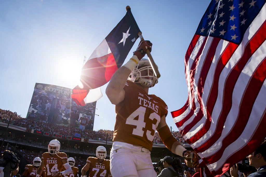 Texas tight end Logan Mills (43) carries the Texas flag as he leads the team onto the field before the 2015 Red River Showdown NCAA football game against Oklahoma at the Cotton Bowl on Saturday, Oct. 10, 2015, in Dallas. (Smiley N. Pool/The Dallas Morning News)
