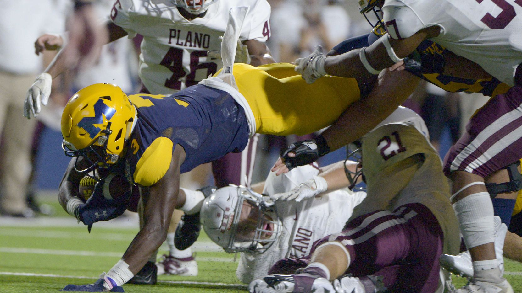 McKinney's Omari Walker reaches for extra yards in the second quarter during a high school football game between Plano and McKinney, Friday, Sept, 25 2020, in McKinney, Texas.