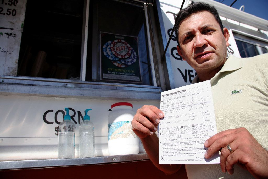 """Carlos Zamora shows a voter registration card from a pile placed on the counter of the Tierra Caliente taco truck on Sept. 29, 2016, in Houston. Zamora is with Mi Familia Vota, a Latino activist group that seeks to register more voters in the Latino community. Mi Familia Vota partnered with a local design firm to make eight of the city's taco trucks into mobile voter registration booths after a surrogate of Republican presidential candidate Donald Trump recently suggested that unless the United States fortifies its borders and tightens immigration limits, """"You're going to have taco trucks on every corner."""" (John L. Mone/The Associated Press)"""
