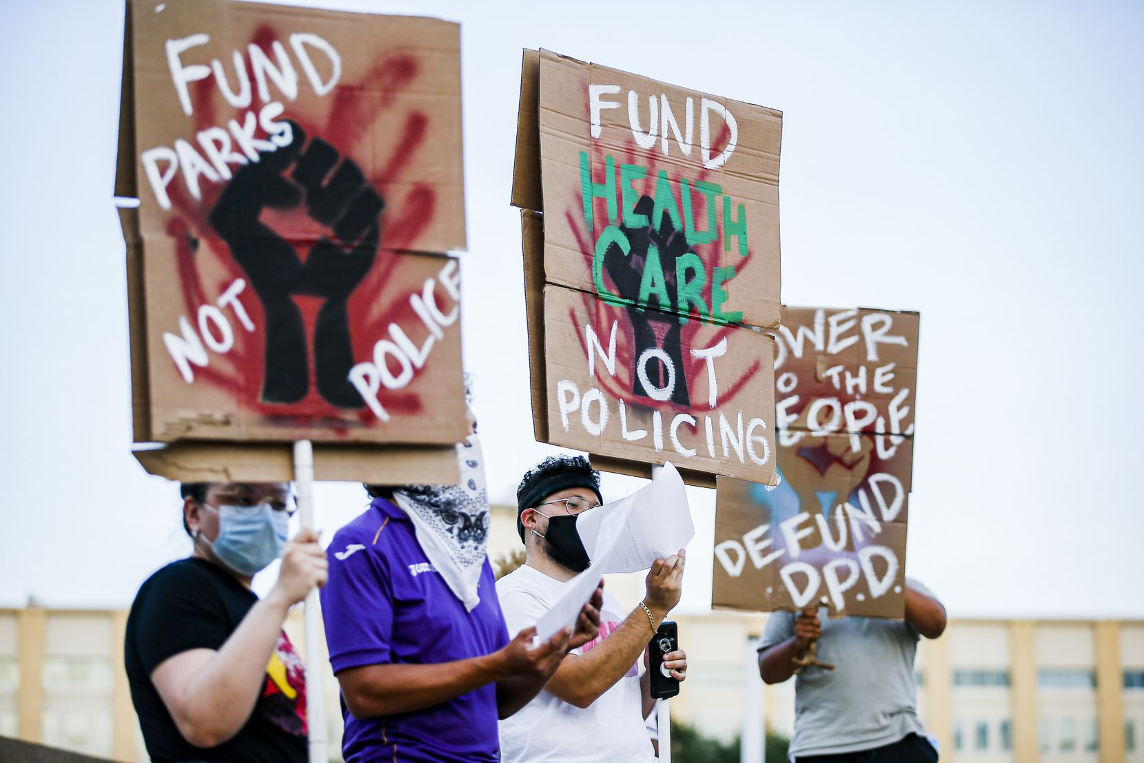 Demonstrators hold up signs demanding that the Dallas Police Departments budget be reduced during a Peoples Town Hall hosted by the In Defense Of Black Lives Dallas organization on the steps of Dallas City Hall in August 2020. The current budget debate is particularly heated due to calls from local activists to cut more money from the police budget — at a time when crime is on the uptick.