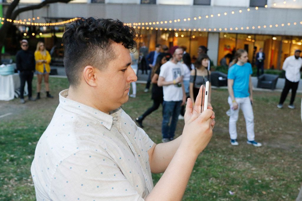 The Artist Uprising Presents: The Dallas Music Experience organizer and promotor Lee Escobedo records the event on his cell phone at Harry C. Beck, Jr. Park in downtown Dallas Friday.