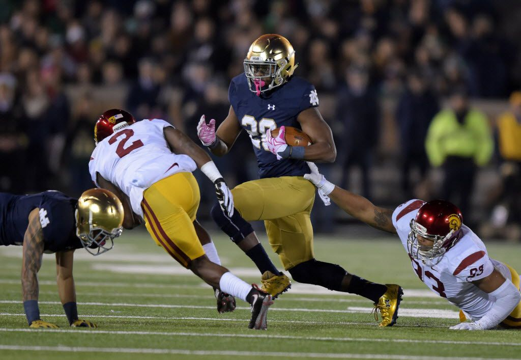 Oct 17, 2015; South Bend, IN, USA; Notre Dame Fighting Irish running back C.J. Prosise (20) is pursued by Southern California Trojans cornerback Adoree Jackson (2) and defensive end Greg Townsend Jr. (93) at Notre Dame Stadium. Mandatory Credit: Kirby Lee-USA TODAY Sports