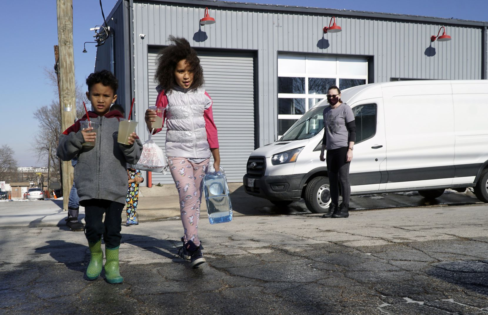Michael Doamekpor (5) and his sister Kiera Doamekpor (9) carry drinks and filtered water to the car at Cowtown Brewing Co. in Fort Worth.