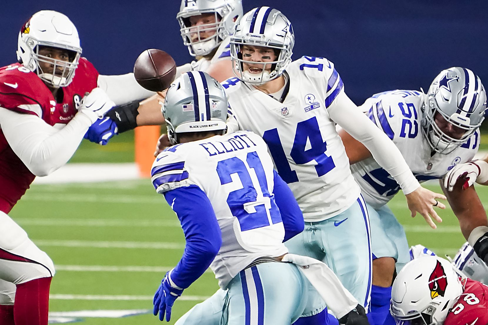 Dallas Cowboys quarterback Andy Dalton (14) gets off a shuffle pass to running back Ezekiel Elliott (21) during the first quarter of an NFL football game against the Arizona Cardinals at AT&T Stadium on Monday, Oct. 19, 2020, in Arlington. (Smiley N. Pool/The Dallas Morning News)