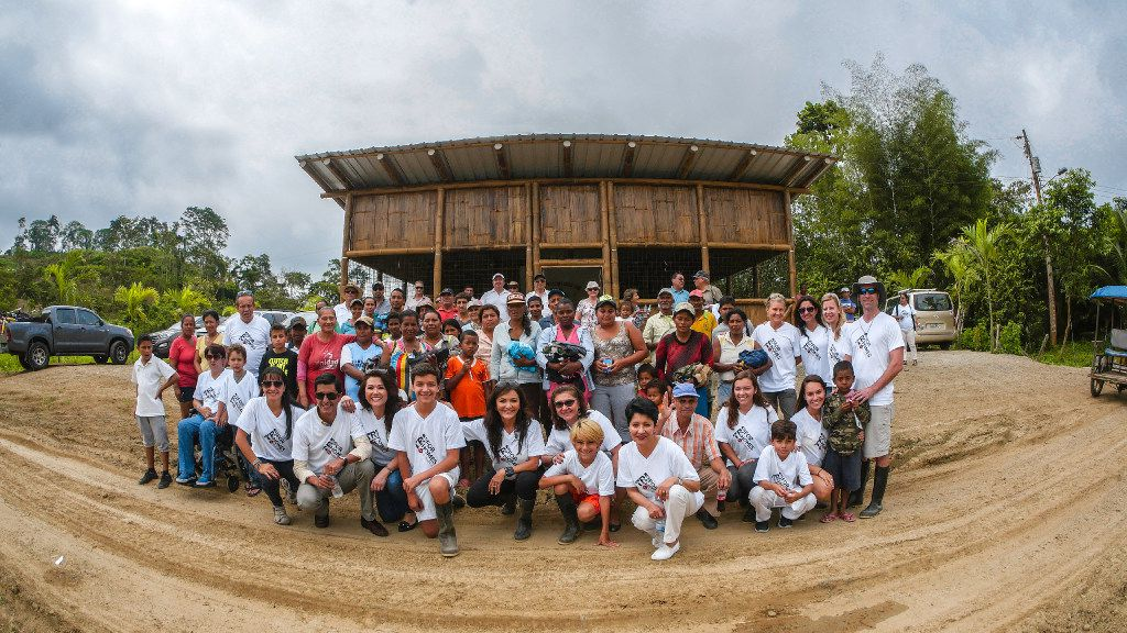 Nina Vaca, CEO of Pinnacle Group, and members of her Tri for Homes team are surrounded by Ecuadorean locals who will live in the 40-home  Villa de la Alegria  (Village of Happiness)   that she s building in Muisne, Ecuador, with the help of the local Rotary Club.