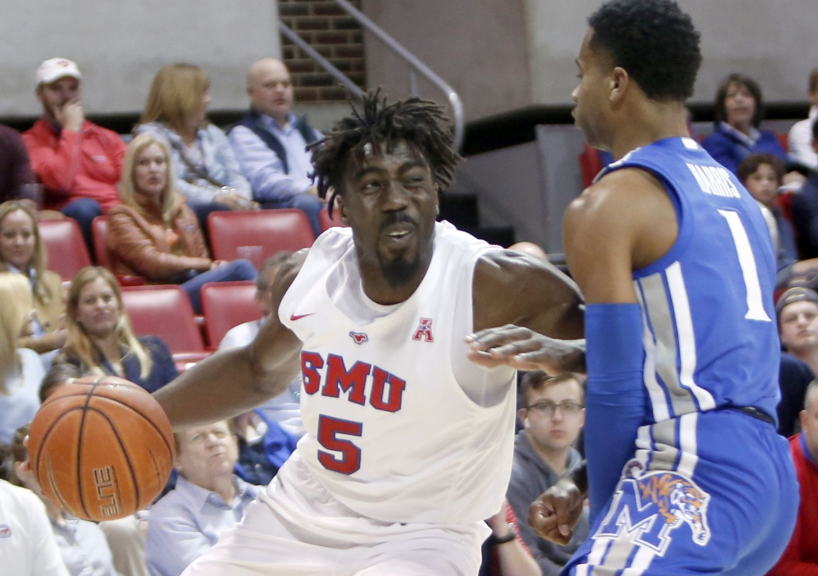 SMU guard Emmanuel Bandoumel (5) drives into Memphis guard Tyler Harris (1) during first half action. SMU defeated memphis 58-53. The two teams from the NCAA's American Athletic Conference played their men's basketball game at SMU's Moody Coliseum in Dallas on February 25, 2020.