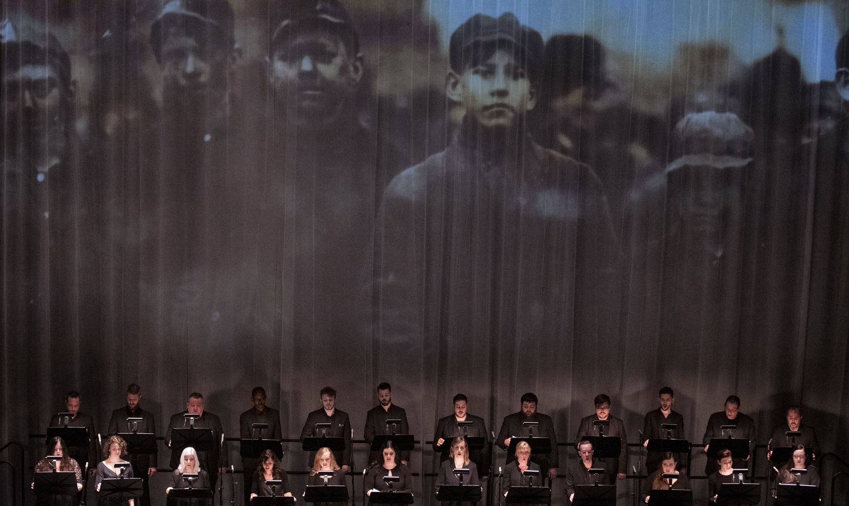 """A photo of young coal miners is projected during the Verdigris Ensemble performance of Julia Wolfe's """"Anthracite Fields"""" at the Dallas Symphony Orchestra's 2019 Soluna International Music and Arts Festival."""
