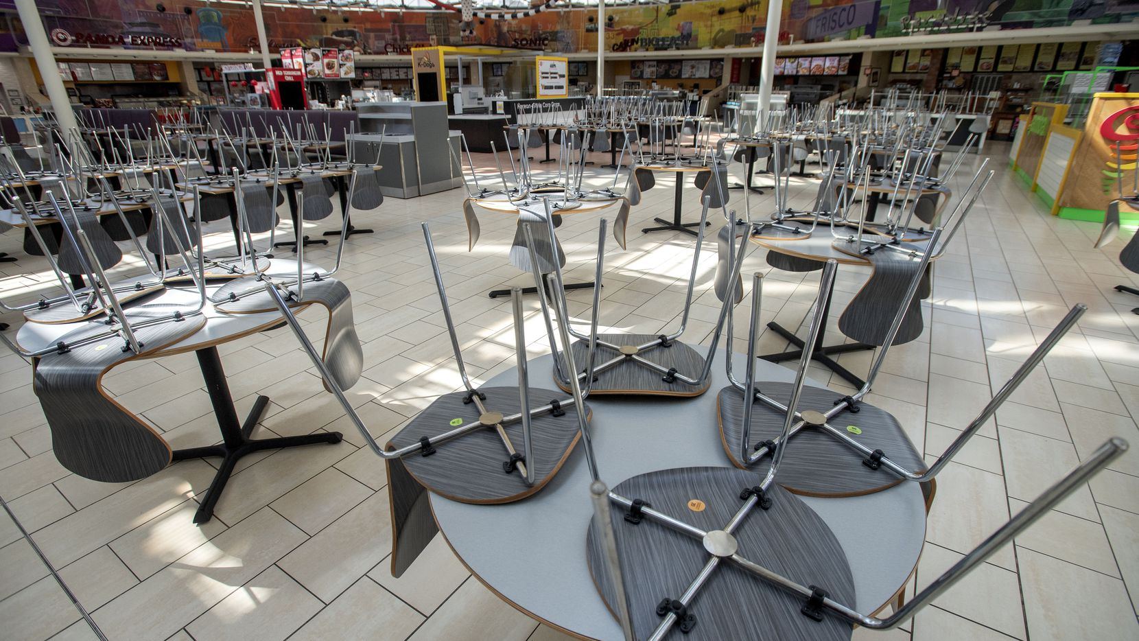 Chairs rest on tables in an empty food court in Stonebriar Mall in Frisco. The coronavirus pandemic has closed many businesses throughout the country and cities like Richardson, which is anticipating $18 million in lost revenue, have begun calculating the local fallout.