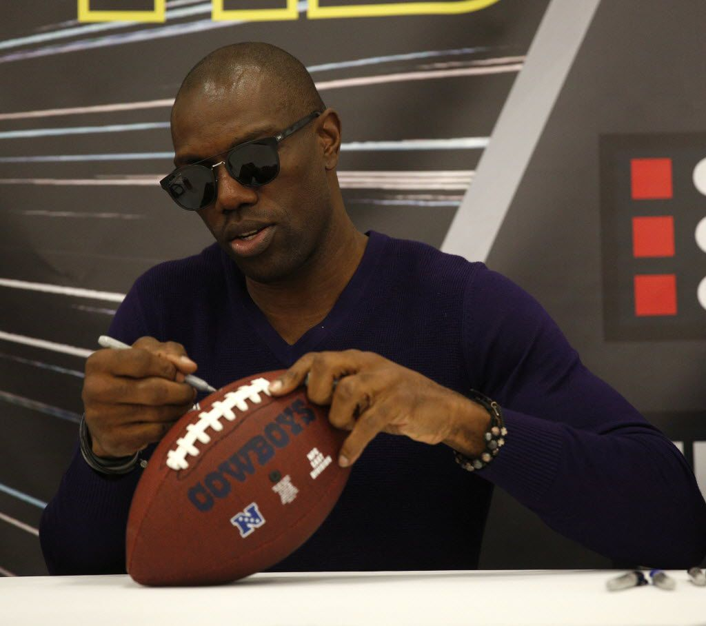 FILE - Former Dallas Cowboy Terrell Owens signs a football at The Ticket Sportradio's Ticketstock 2016 at the Irving Convention Center in Irving, Texas on Feb. 20, 2016. (Rose Baca/The Dallas Morning News)